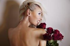 Femme blonde gaie avec des fleurs Photographie stock libre de droits