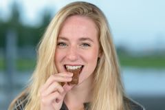 Femme blonde gaie mangeant du chocolat photo stock
