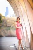 Femme blonde grande se tenant dans la robe de corail de licou devant le Pavillion près de Lincoln Park Zoo Chicago, l'Illinois Photo stock