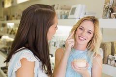 Femme blonde heureuse appliquant les produits cosmétiques Photo stock