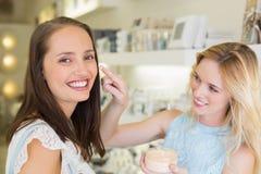 Femme blonde heureuse appliquant les produits cosmétiques sur son ami photographie stock