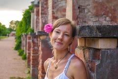 Femme blonde heureuse avec la fleur rose dans ses cheveux se tenant devant le mur de briques sur le chemin de parc image stock