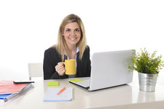 Femme blonde heureuse d'affaires travaillant sur l'ordinateur portable d'ordinateur avec la tasse de café Photos stock