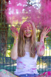 Femme blonde heureuse jetant en l'air vers le haut de la poudre rose Holi en parc Image libre de droits