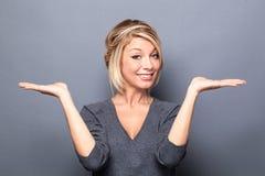 Femme blonde heureuse montrant quelque chose égale sur les mains vides Photographie stock