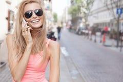 Femme blonde heureuse parlant par le téléphone portable Image stock