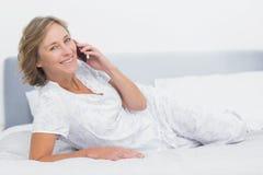Femme blonde heureuse se trouvant sur le lit faisant un appel téléphonique images stock