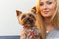 Femme blonde heureuse sensuelle s'asseyant sur le banc en bois avec son chien Images libres de droits