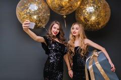 Femme blonde inspirée tenant le grand présent bleu et souriant à la fête d'anniversaire Fille de charme dans la robe noire faisan image stock