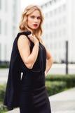 Femme blonde intelligente tenant sa veste sur le fond de centre d'affaires Images stock