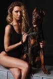 Femme blonde magnifique dans une combinaison noire avec le dobermann regardant l'appareil-photo Belle fille avec de longues jambe Photo stock