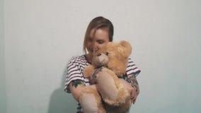 Femme blonde mignonne dans la chemise rayée avec des tatouages, caressant avec le jouet d'ours de nounours banque de vidéos