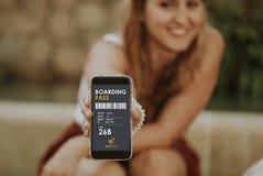 Femme blonde mignonne montrant la carte d'embarquement électronique dans un téléphone portable Photographie stock