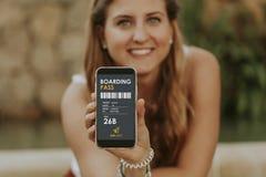 Femme blonde mignonne montrant la carte d'embarquement électronique dans un téléphone portable Photo stock