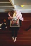 Femme blonde mignonne s'asseyant à la maison sur le plancher avec un ordinateur sur son recouvrement Photographie stock libre de droits