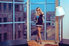 Femme blonde mince adorable avec la tasse de thé par la grande fenêtre W Photos libres de droits