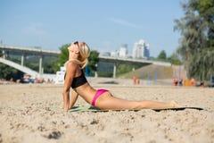 Femme blonde mince caucasienne faisant des excercises de yoga à la plage images stock