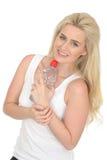 Femme blonde naturelle en bonne santé d'ajustement heureux jeune tenant une bouteille de l'eau minérale Image libre de droits