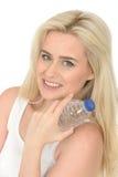 Femme blonde naturelle en bonne santé d'ajustement heureux jeune tenant une bouteille de l'eau minérale Images libres de droits