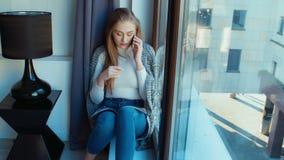 Femme blonde parlant au téléphone par la fenêtre banque de vidéos