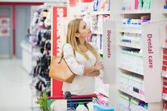 Femme blonde pensant aux produits images stock