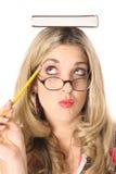 Femme blonde pensant avec le livre sur la bouche principale images stock