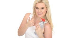 Femme blonde positive en bonne santé d'ajustement heureux jeune tenant une bouteille de l'eau minérale Photo stock