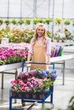Femme blonde poussant le chariot avec des fleurs image libre de droits
