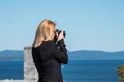 Femme blonde prenant des photographies Photo stock
