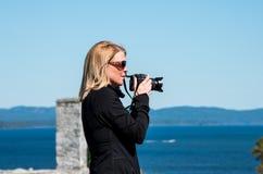 Femme blonde prenant des photographies Photographie stock