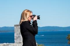 Femme blonde prenant des photographies Photographie stock libre de droits