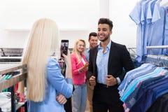 Femme blonde prenant la photo des jeunes faisant des emplettes, clients de sourire heureux d'amis dans la boutique de mode Photographie stock libre de droits