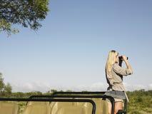 Femme blonde regardant par des jumelles dans la jeep Images stock