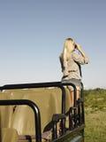 Femme blonde regardant par des jumelles dans la jeep Photos stock