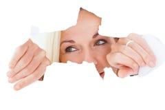 Femme blonde regardant par le papier déchiré Images libres de droits