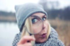Femme blonde regardant par une loupe image libre de droits