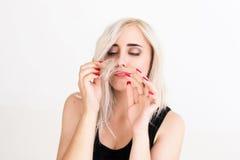 Femme blonde regardant ses astuces de cheveux photo stock