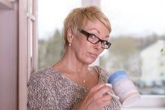 Femme blonde sérieuse avec des verres tenant une tasse Images libres de droits