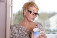Femme blonde sérieuse avec des verres tenant une tasse Photo stock