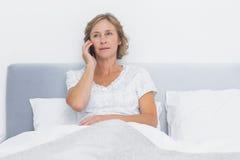 Femme blonde sérieuse faisant l'appel téléphonique dans le lit photographie stock libre de droits