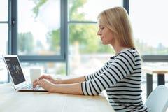 Femme blonde sérieuse se concentrant sur son travail Photos stock