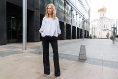 Femme blonde sérieuse se tenant dans la pleine croissance sur la ville de rue images stock