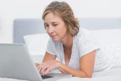 Femme blonde sérieuse se trouvant sur le lit utilisant l'ordinateur portable photo libre de droits