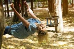 Femme blonde s'asseyant sur une oscillation dans le terrain de jeu photographie stock libre de droits