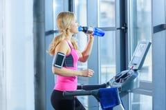 Femme blonde s'exerçant sur le tapis roulant et l'eau potable  Image stock