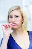 Femme blonde se brossant les dents photos stock