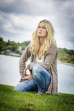 Femme blonde se mettant à genoux au lac Image libre de droits