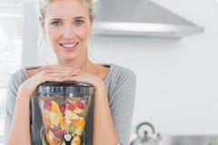 Femme blonde se penchant sur son presse-fruits et souriant à l'appareil-photo Photographie stock libre de droits