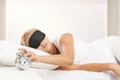 Femme blonde se réveillant dans sa chambre à coucher Image stock