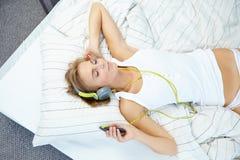 Femme blonde se trouvant sur le lit tandis que musique de écoute Photographie stock
